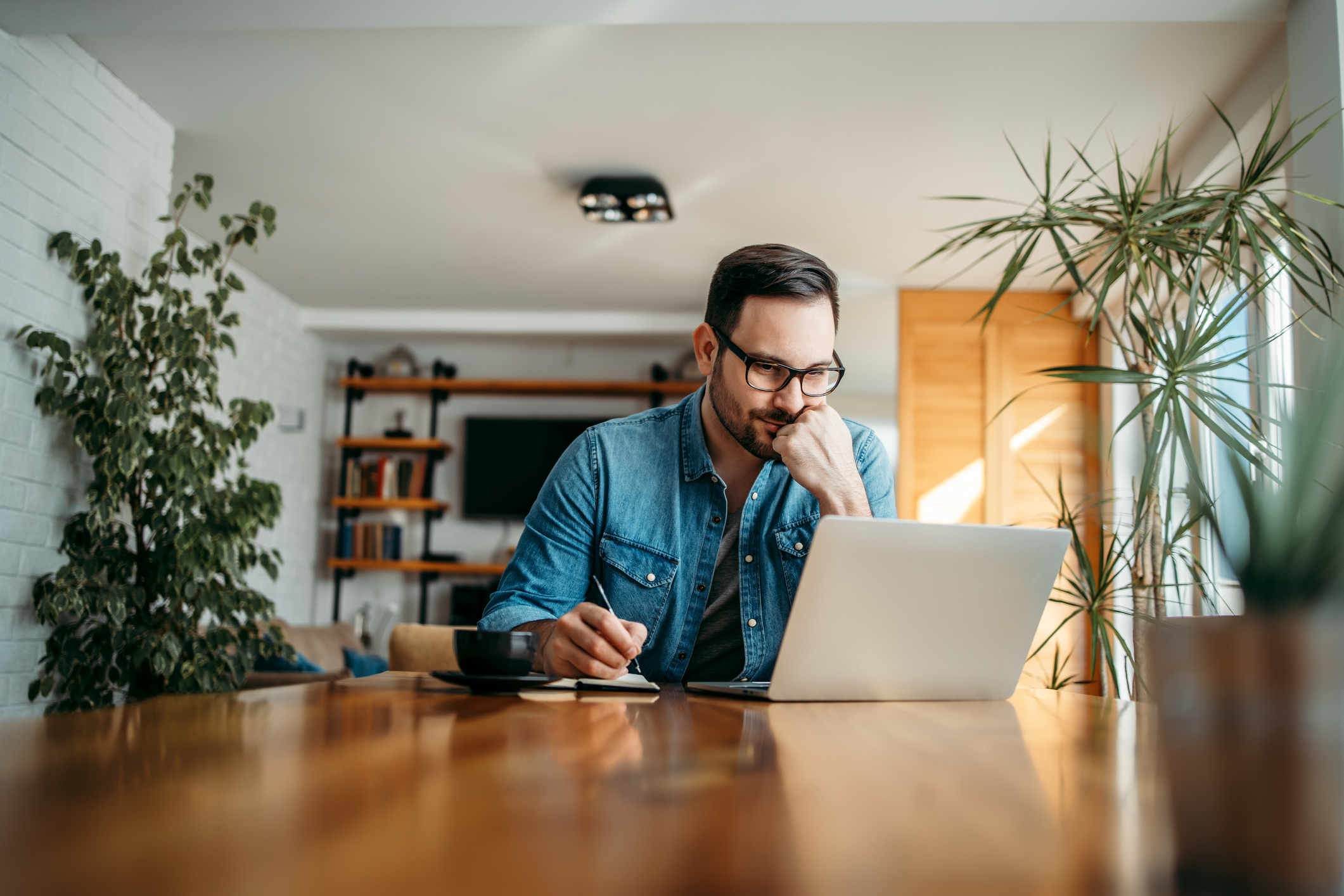 Man looking at computer and taking notes