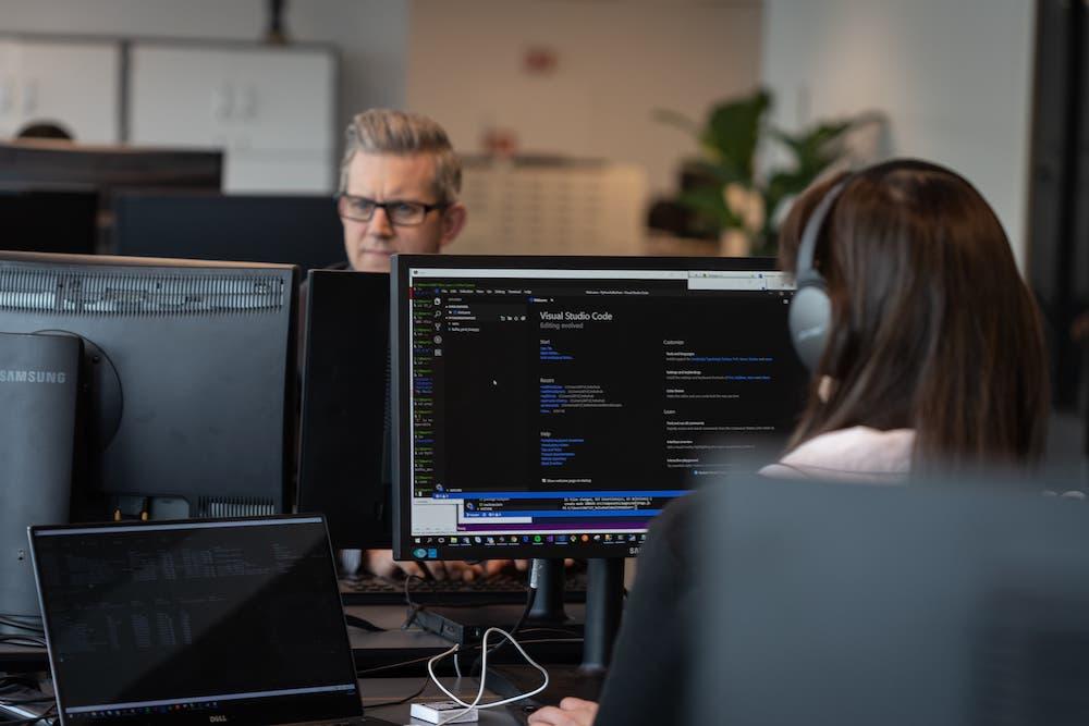 Skjerm med kode-program med mann i bakgrunnen