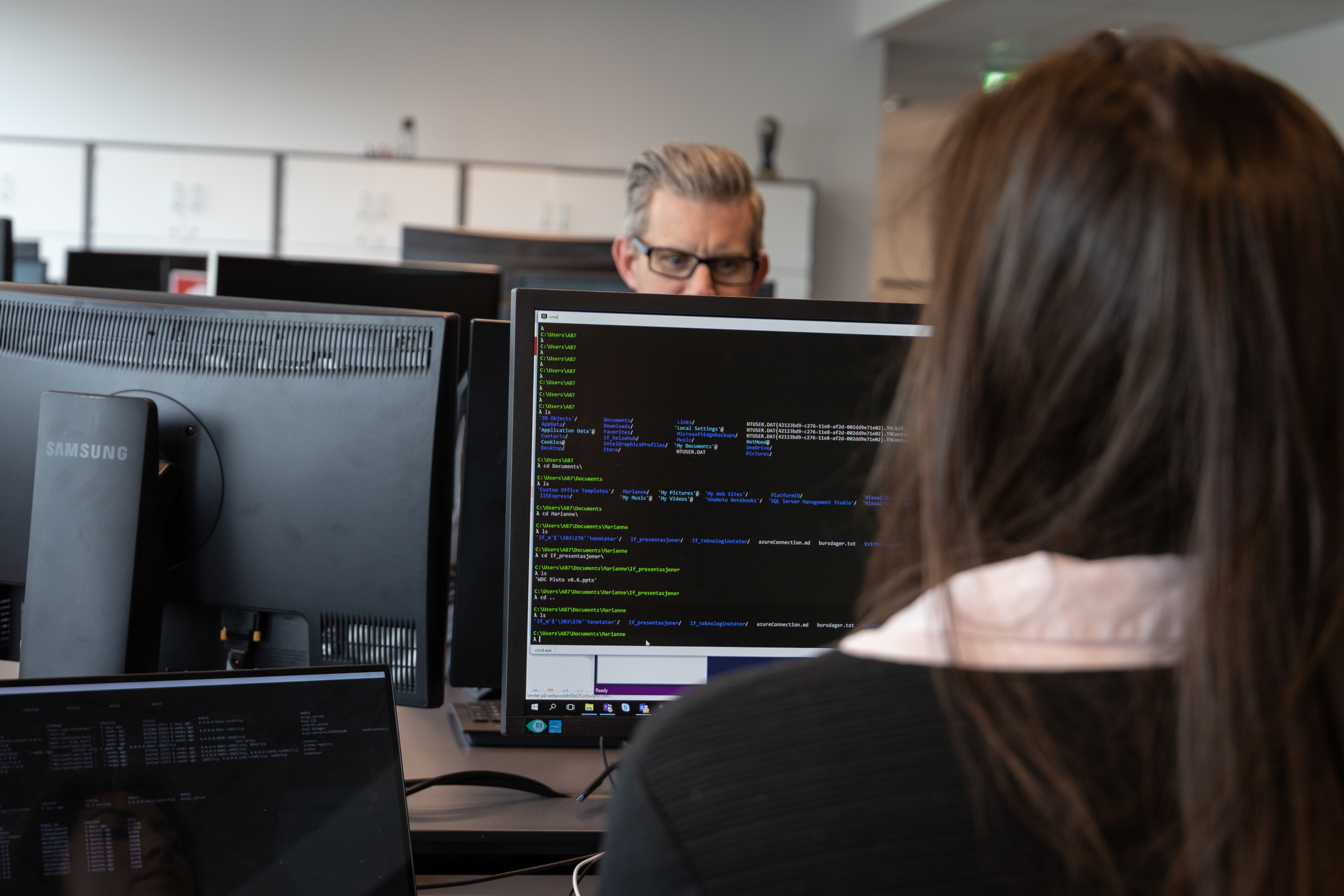 Screen with code, man in background